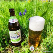 yellow beer in glass with big head and bottle next to flowers in grass