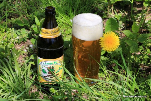 yellow beer in glass next to bottle and flower on grass