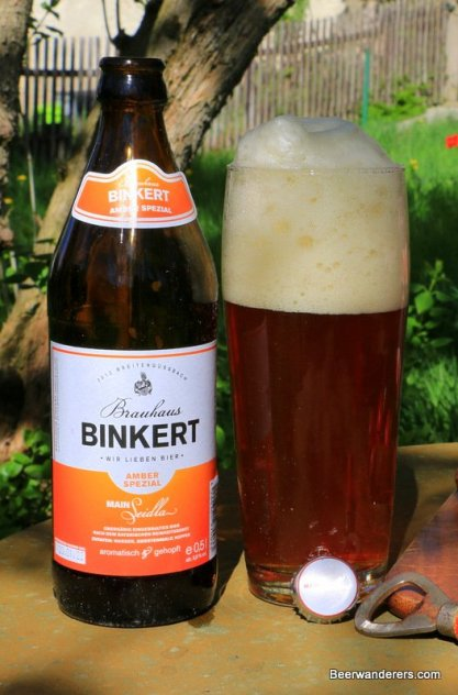 unfiltered amber beer in glass with huge head and bottle