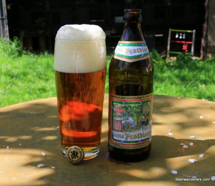 beer in glass with big head and bottle