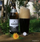 dark beer in glass with huge head and bottle with flower