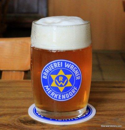light amber beer with huge head in logo mug