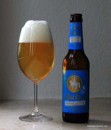 unfiltered golden beer in wine glass with bottle