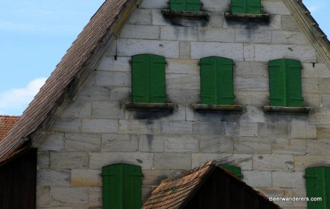 stone building with green wooden shutters