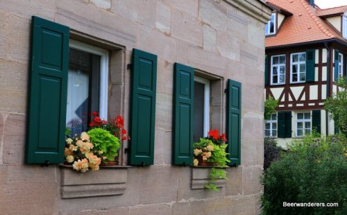 stone house with shutters and flowers