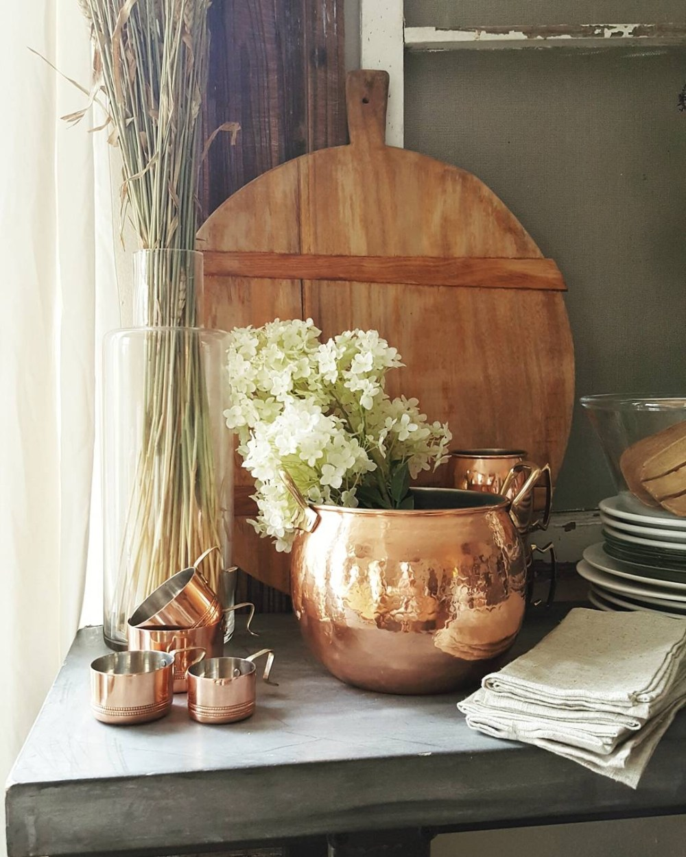 Country Farmhouse Kitchen White Tulips Flowers Wood Spoons Bread Boards Concrete Table Copper Hydrangea Metrie Moulding Molding Baskets Country Living Decor Design