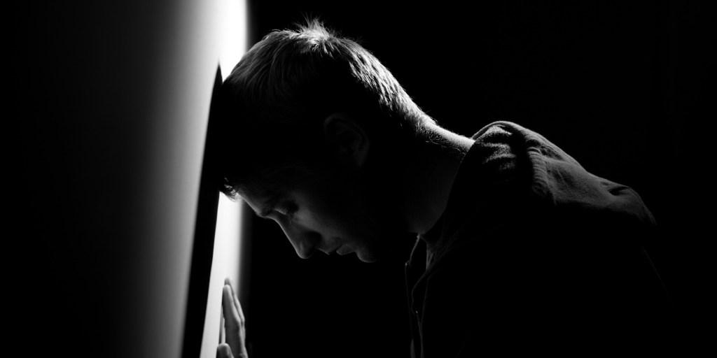 depression man head on wall