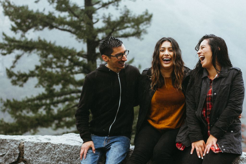 A man and two women,closely seated on a fence, hugging one another, happy and laughing.
