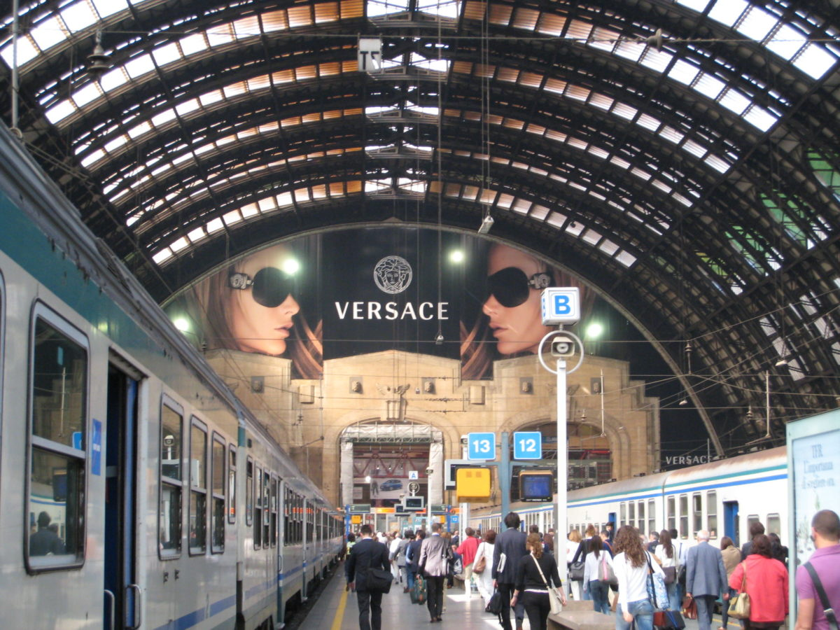 Milan Central Station, view from platform to main station with large Versace ad near the ceiling