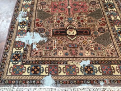 fine handmade persian rug with extensive moth damage