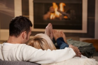 Young-couple-hugging-on-sofa-in-front-of-fireplace-at-home