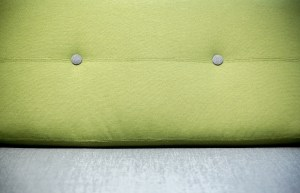 Close up of a sofa with a green cushioned back and a light grey seat.