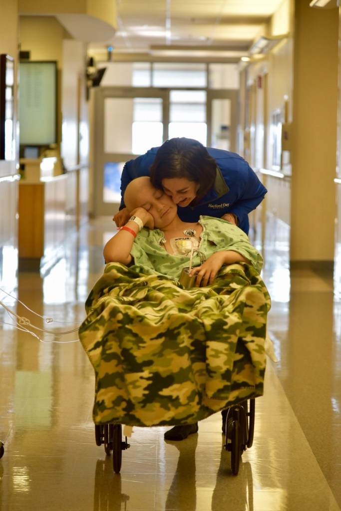 Mom embracing child who is apart of the Believe In Tomorrow program