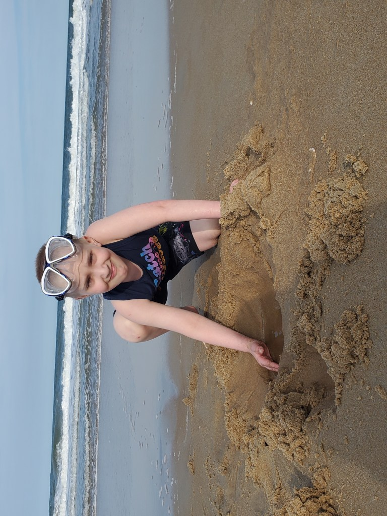 A critically ill child playing in the sand on a respite trip