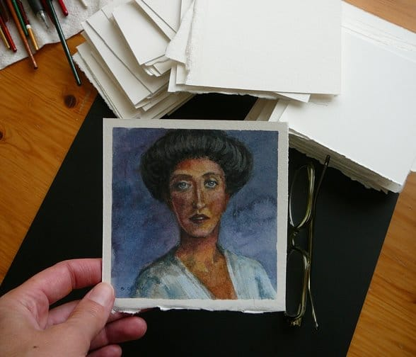 a stack of watercolor paper squares, and a tiny portrait of a woman on one of the sheets
