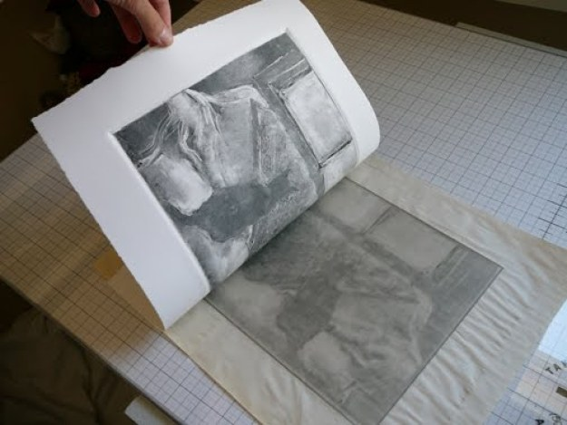 pulling a sheet of paper from a plexiglass plate with ink transferred from the plate to the paper via pressure on a press