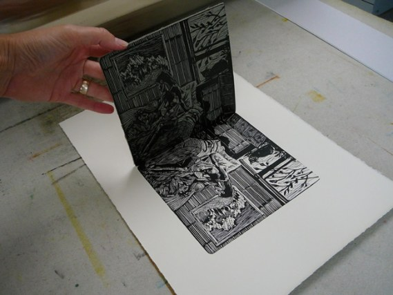 pulling a linoleum block after transferring ink to paper on a press