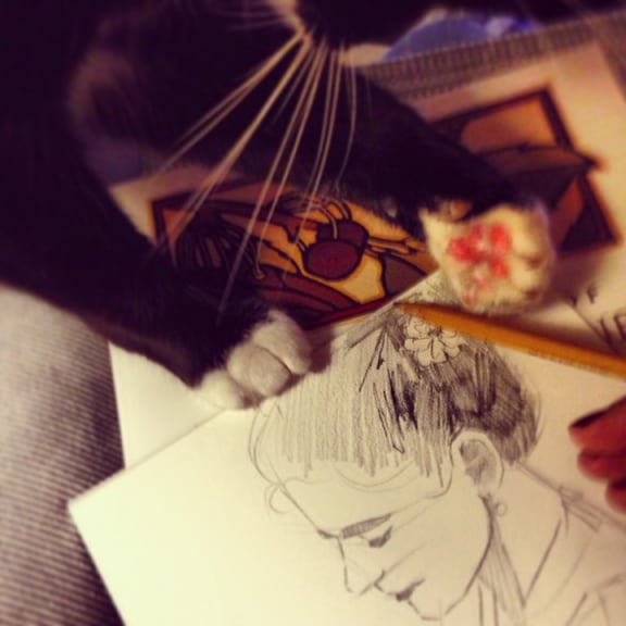 Sketching with pencil on mat board to make a collagraph with a cat swatting at the pencil