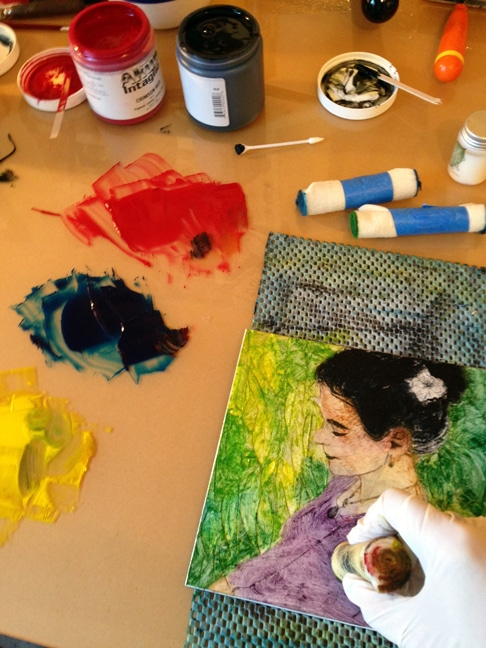 applying different colors of ink to the collagraph plate with a felt dauber