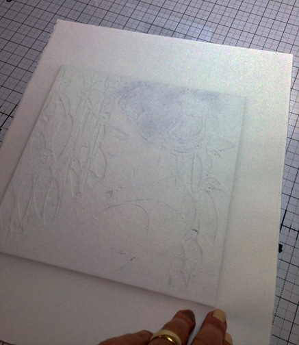 printmaking paper pressed against an inked plate on a press, leaving embossed shapes on the verso of the paper