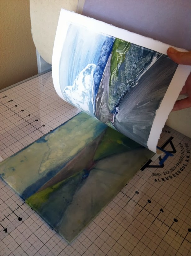 pulling a print in full color, of a landscape, from a sheet of wet ink on an etching press bed
