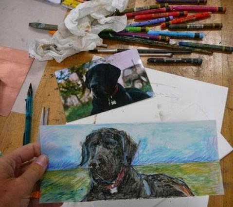 Making the monotype on a table with a reference photo of a black great dane and a pile of caran d'ache crayons strewn about