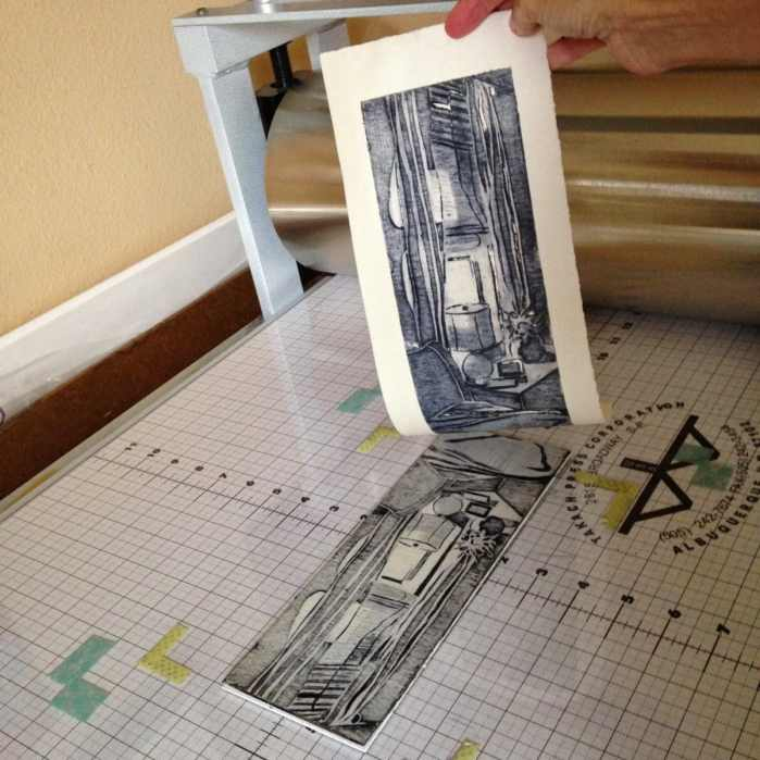 after pressing paper against the carved and inked mat board, the print is pulled from the surface showing that ink has been transferred from the plate to the paper