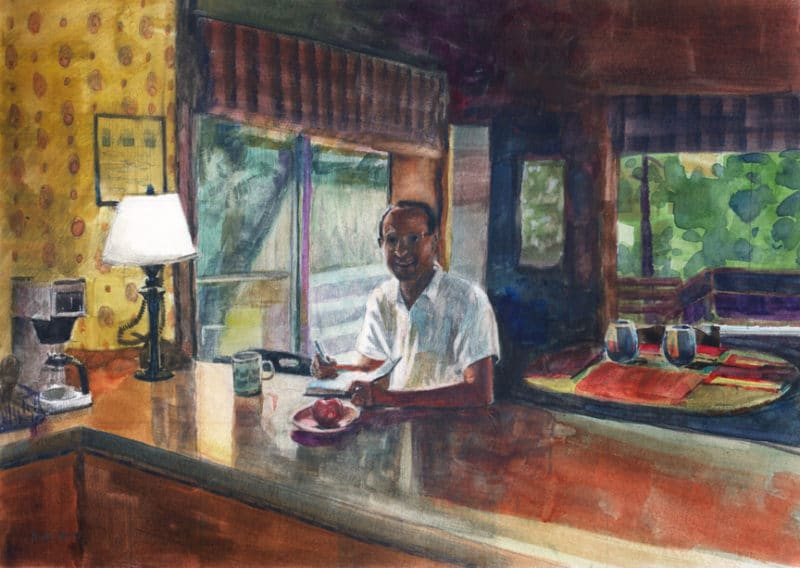 a man sitting at a kitchen counter writing in a book with a cup of coffee and an apple on a plate and slanted sunlight streaming into the room behind him
