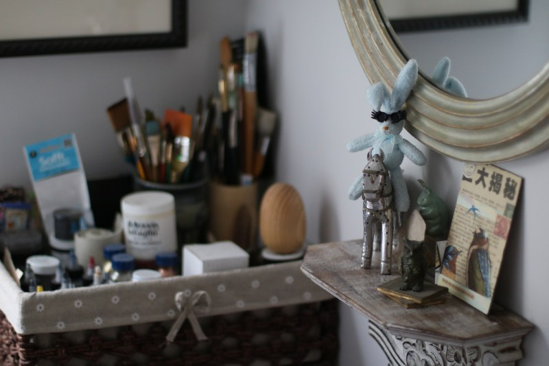 A basket of inks and paint brushes, and a shelf with a tin house, stuffed rabbit, cast iron owl