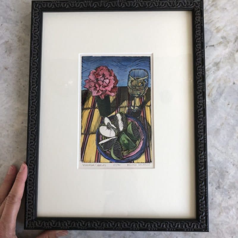 a colorful still life linocut of a rose, a glass of wine and sliced apples in a frame