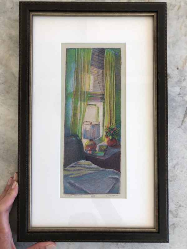 a matted and framed collagraph print of a bedroom interior with a window and a bed in filtered light