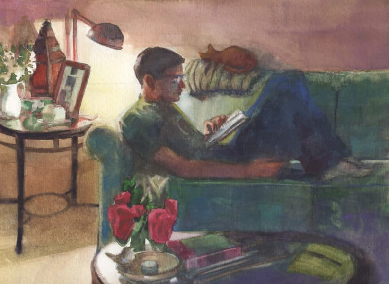a boy reading a book on a couch near a single lamp in a cozy room with a cat