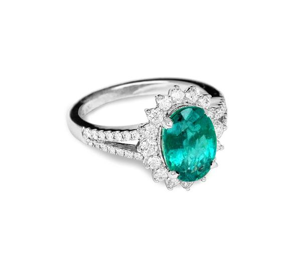 A white gold womens ring with a large emerald and small round diamonds