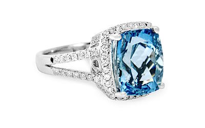 close up of white gold ring with diamonds and a large aquamarine gemstone