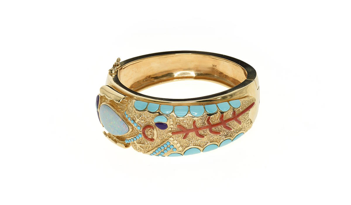A thick gold bracelet with a corn maiden design made out of gemstones