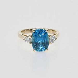 a gold ring with diamonds and zircon gemstone
