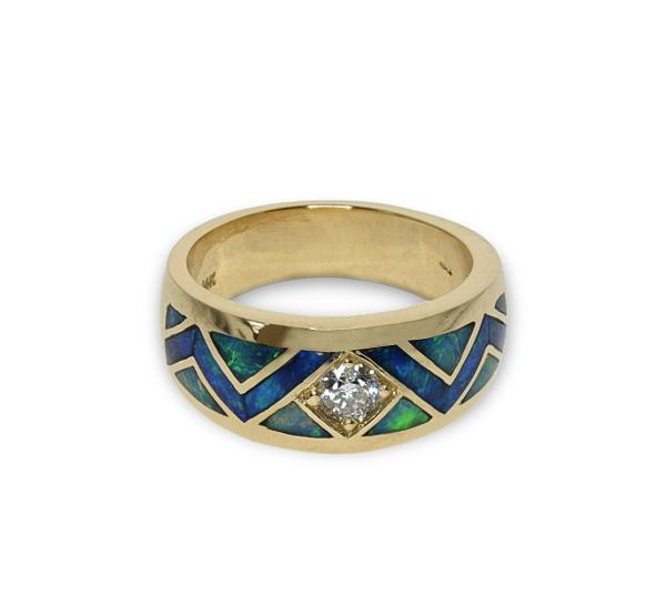 A Gold band featuring a center diamond and opal inlay