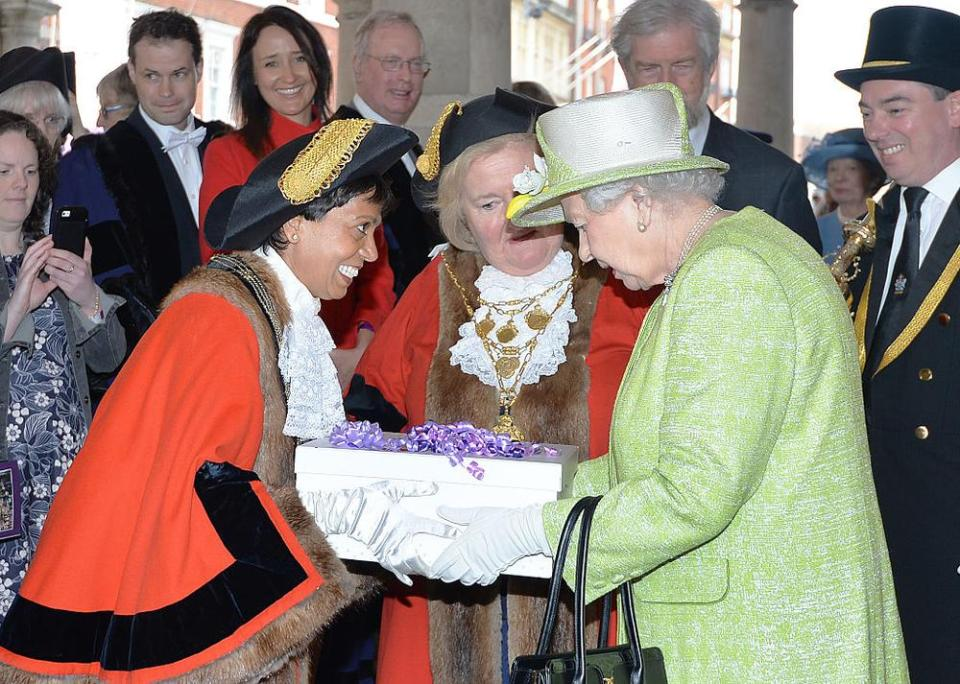 WINDSOR, ENGLAND - APRIL 21: Queen Elizabeth II receives a gift during her 90th Birthday Walkabout on April 21, 2016 in Windsor, England. Today is Queen Elizabeth II's 90th Birthday. The Queen and Duke of Edinburgh will be carrying out engagements in Windsor. (Photo by John Stillwell - WPA Pool/Getty Images)