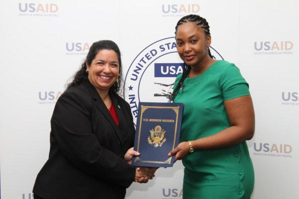 DCM, Maria E. Brewer presents Chinwe Osuji of Babban Gona with signed agreements