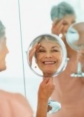 6351299-portrait-of-a-smiling-elderly-woman-looking-at-herself-in-a-handheld-mirror
