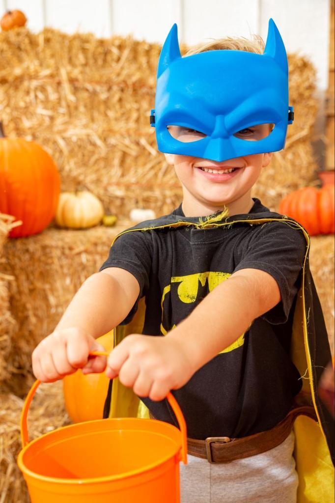 boy in blue batman mask with orange pale