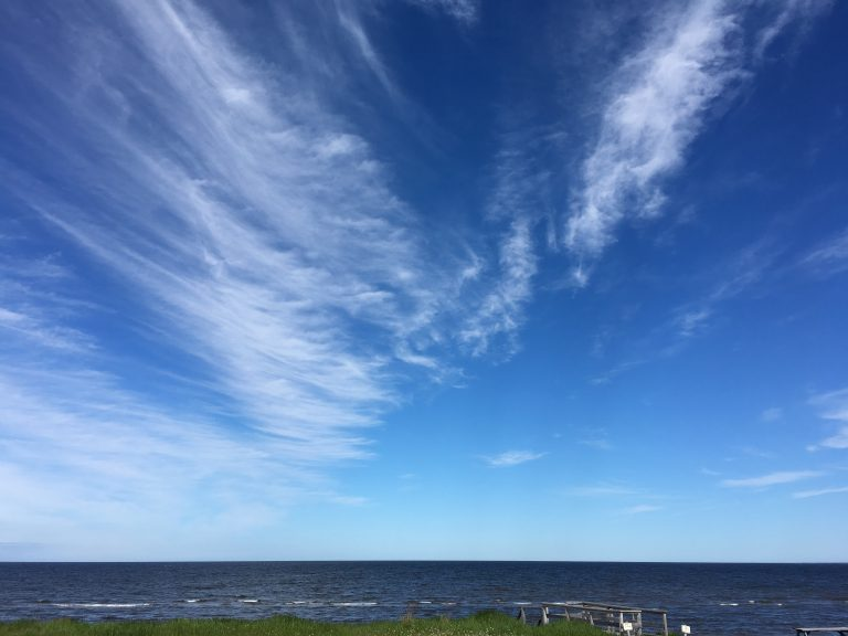 Beautiful blue skies and angel wing clouds over the sea at Cocagne, New Brunswick.