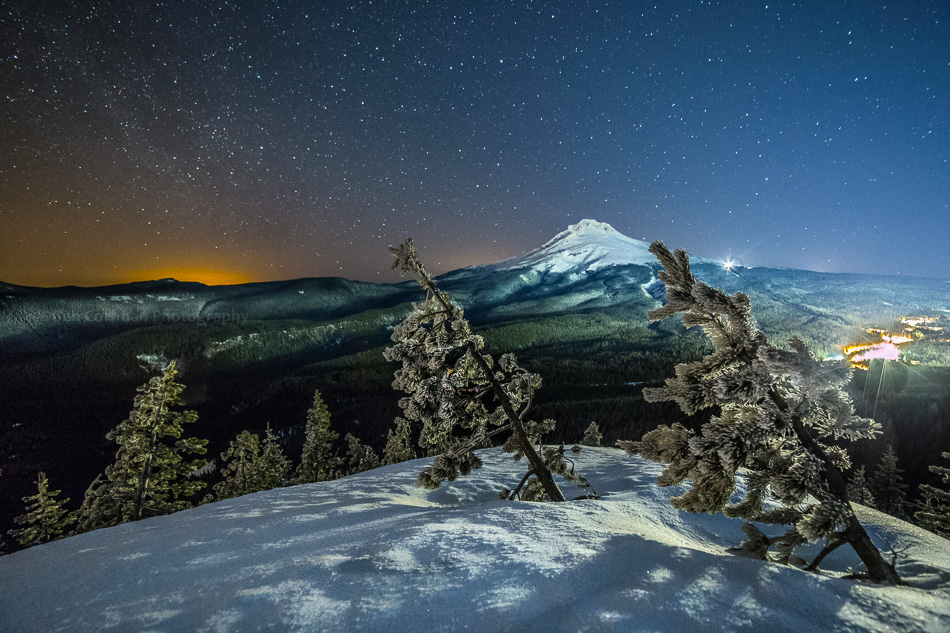 A snowy Mt Hood sits with stars above it.