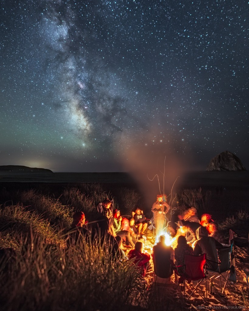 A group of beachgoers sits around a bonfire under the Milky Way, Oregon coast.
