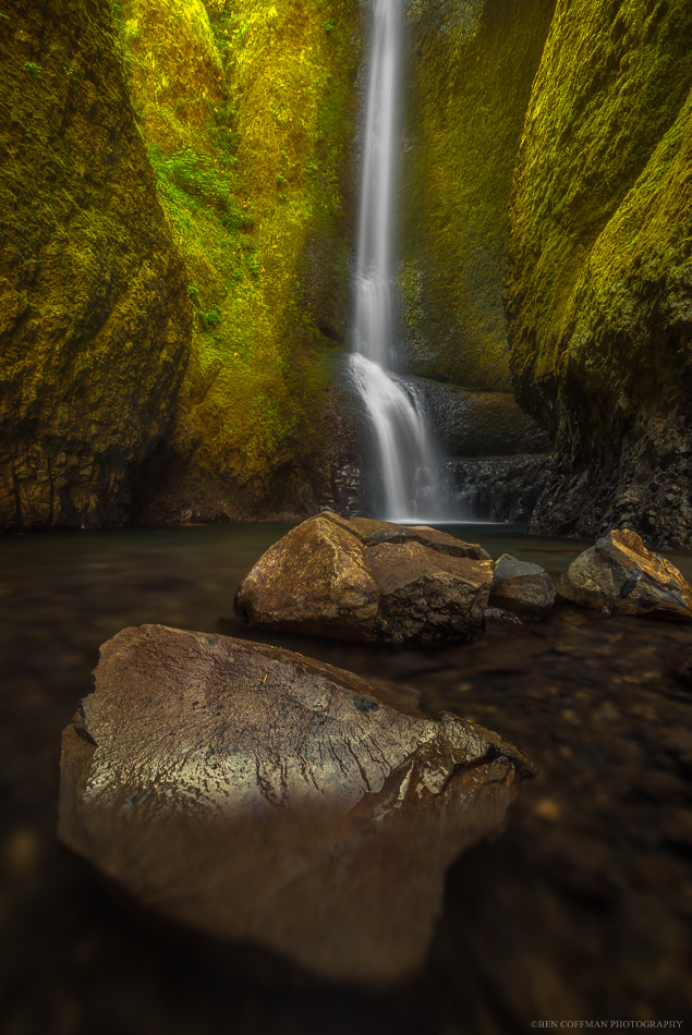 Rocks sit beneath a waterfall in Oneonta Gorge