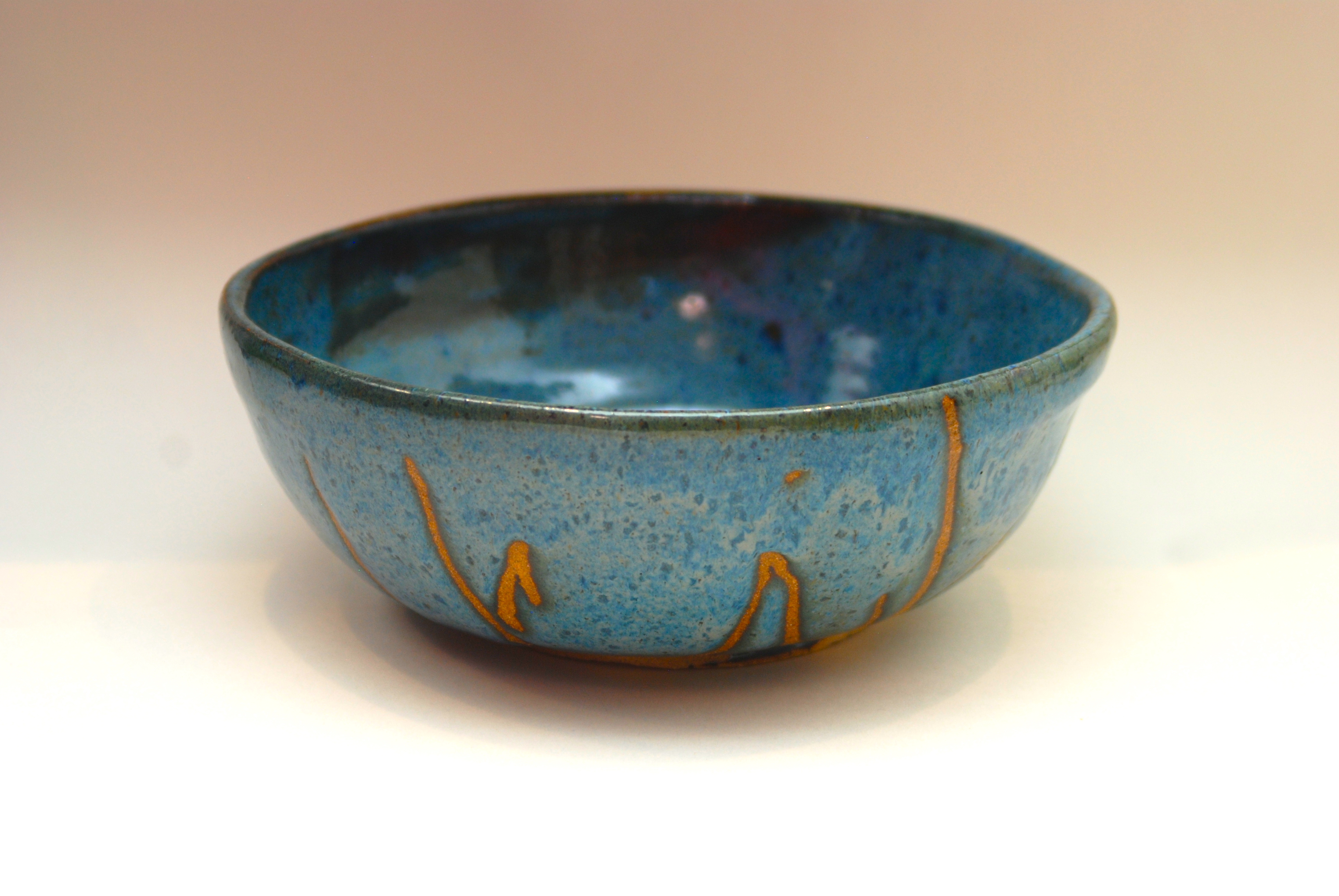 hand thrown pottery with blue glaze and wax designs