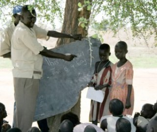 Bol Deng teaches the children with a slab of chalkboard