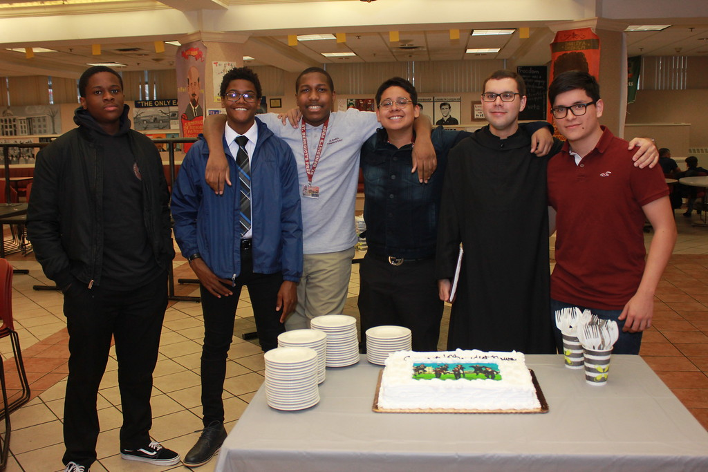 BNews Banquet: Br. Asiel Rodriguez, O.S.B., second from right, convinces BNews staffers to wait til after dinner to eat the cake. (From left) Jonathan Dulce, Seun Eisape, Israel Small, Yannie Lopez, Br. Asiel,, and Kevin Calle.