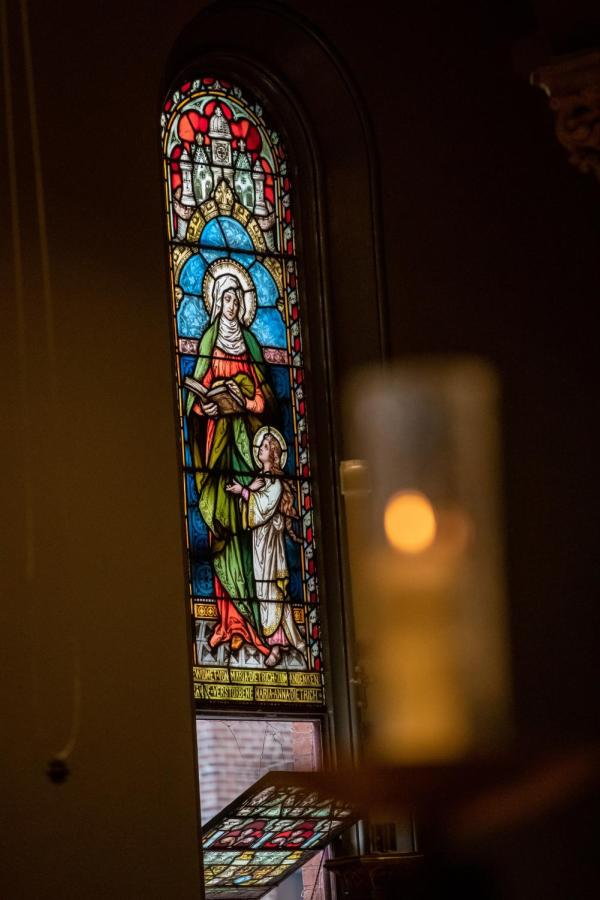 A warm summer breeze wafts through the tilted bottom half of the 19th century German stained glass windows.