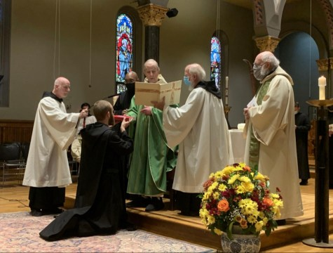 """Newark Abbey Abbot Melvin Valvano, O.S.B, presents Br. Bruno with his personal copy of """"The Rule"""" during the young monk's profession."""